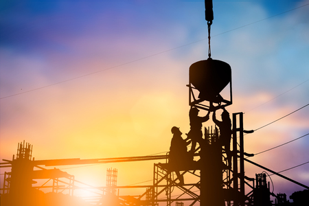 Silhouette engineer Good team work, quality work securely over blurred natural background sunset pastel. Heavy industry and safety at work concept.
