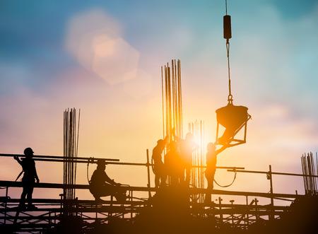 높은, 책임자 엔지니어, 건설 또는 흐리게 파스텔 배경 위에 계획에서 일몰 작업 산업 건설 노동자의 실루엣. 중공업 개념입니다.