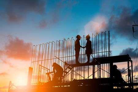 Success of the joint venture business growth, progress and potential concepts.Silhouette businessmen shake hands finishing a deal between businesses over blurred employees at Construction Site.flare light