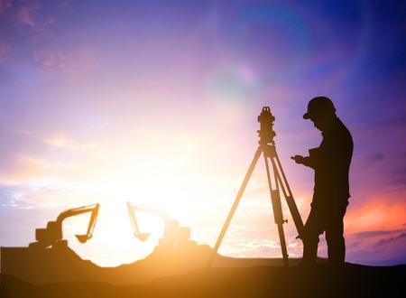 ingeniero encuesta silueta trabajando en una obra de construcción más trabajador de la construcción borrosa en el sitio de construcción Foto de archivo
