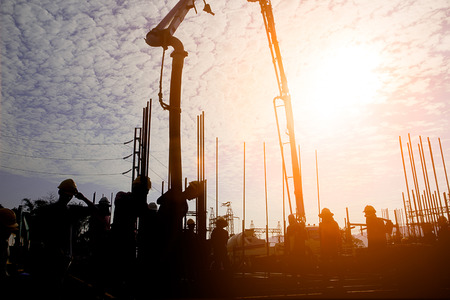 Silhouette construction industry team safely to work load concrete building according to set goal over blurred background sunset pastel for industry background. 版權商用圖片