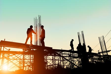 Silueta órdenes Ingeniero de pie para los equipos de construcción para trabajar de forma segura en un terreno elevado sobre el fondo borroso natural de la puesta del sol en colores pastel. la industria pesada y la seguridad en el concepto de trabajo. Foto de archivo - 81958585