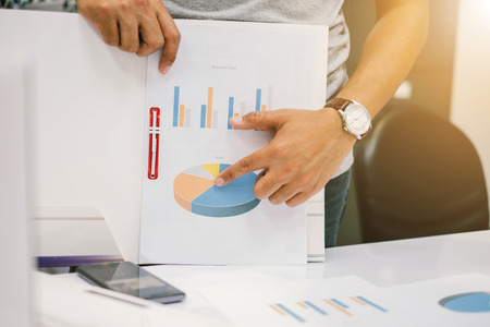 Young businessmen presenting graphs at the quarterly performance report over blurred office. select focus and Film Tone with Light fair Stock Photo
