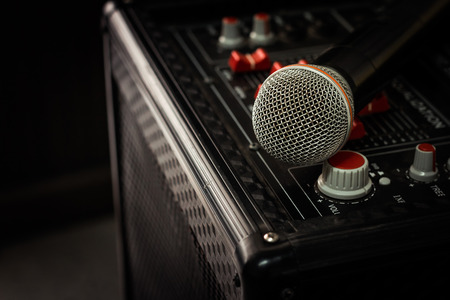 synthesiser: Microphone in soft focus placing on audio synthesiser electronic music instrument sound mixer machine in blur meeting room: Metallic material mic for vocal entertainment in seminar auditorium hall