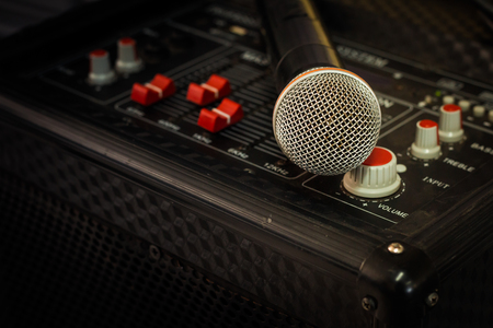 Microphone in soft focus placing on audio synthesiser electronic music instrument sound mixer machine in blur meeting room: Metallic material mic for vocal entertainment in seminar auditorium hall