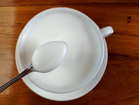 Melk in een witte kop op de houten tafel en iemand likt melk met een zilveren lepel.