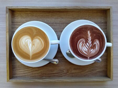Hot latte and cocoa in white cups on the wood table at the coffee shop. Latte art coffee. 写真素材