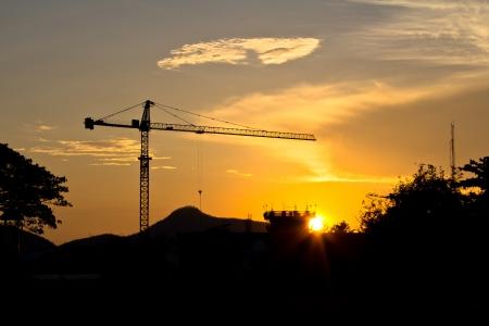 Industrial landscape  Construction cranes and concrete structure at silhouettes sunset   Archivio Fotografico