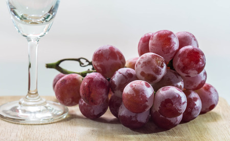 Fresh grapes with wine glass isolated on white