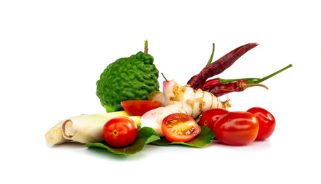 Ingredients Thai spicy soup (Tom-yum) include lemongrass, lime, kaffir lime, tomato,chilli pepper,Galangal on white background. Stock Photo