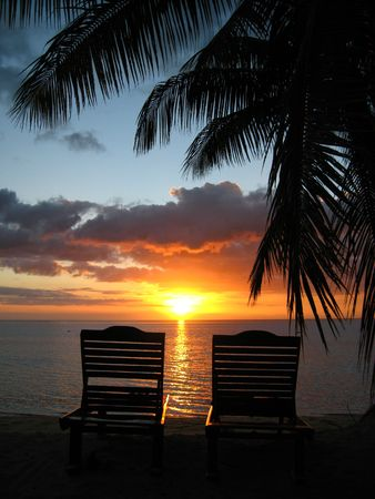 Two deckchairs on beach at sunset photo