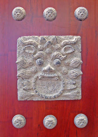 Red chinese door with a lion head                                photo