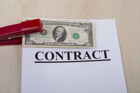 bind: contract and money fastened by a stapler