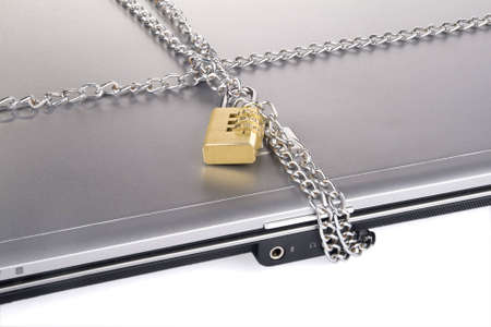 Laptop with chains and combination padlock isolated on white photo