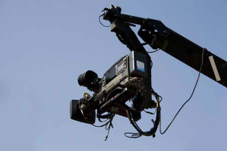newscast: TV camera on the crane and with blue sky in the background