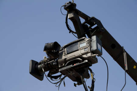 newsroom: TV camera on the crane and with blue sky in the background