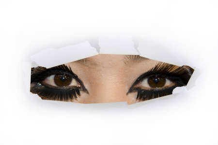 a woman eyes looking through cut paper hole photo
