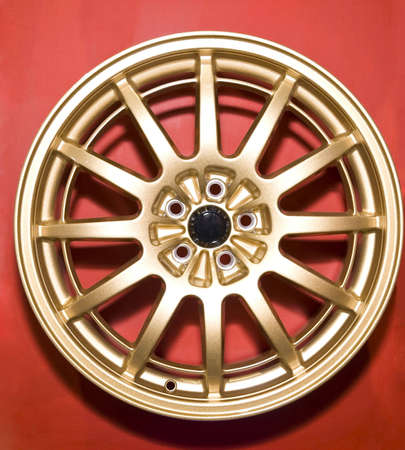 hubcap: a golden hubcap isolated over red background