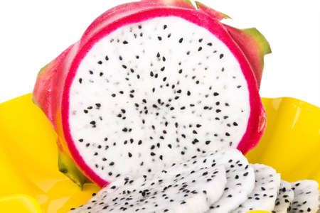 A ripe Dragon Fruit on a plate in the yellow plate photo