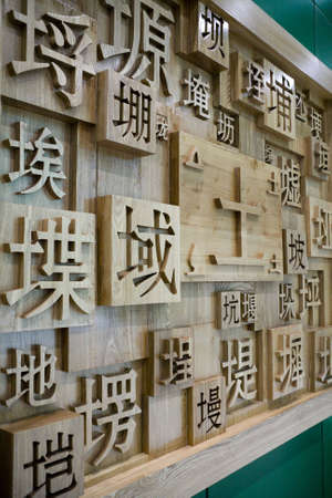 script: Chinese characters soil sign engraved on wood  Stock Photo