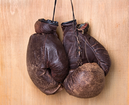 combative: old boxing gloves hang on nail on wall Stock Photo