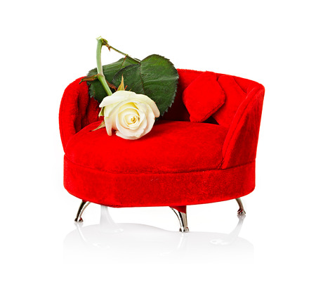 Red sofa, couch with white rose close-up isolated Stock Photo - 25398485