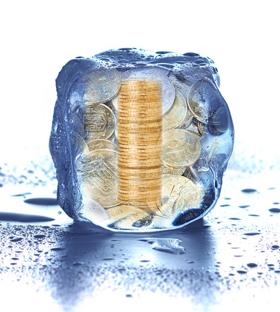 Stack of coins in the ice cube  frozen accounts photo