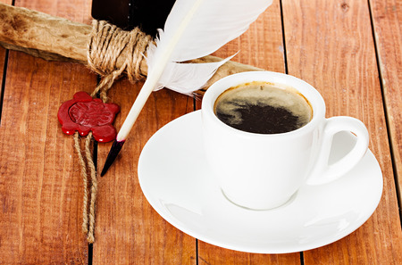 cup of coffee with a quill pen and ink scroll on wooden background photo
