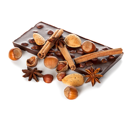 Chocolate and nuts with cinnamon sticks, star anise isolated photo