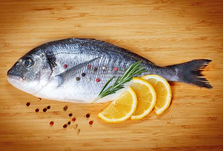 Fresh fish dorado on wooden background photo