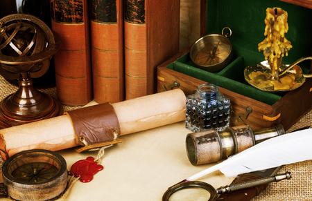 Livres anciens, stylo plume et bouteille d'encre, vieux défilement avec cachet de cire rouge, boussole millésime. histoires d'aventure fond. Style rétro.