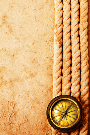 stale: Ancient brass compass with rope on vintage old paper background. Retro stale.