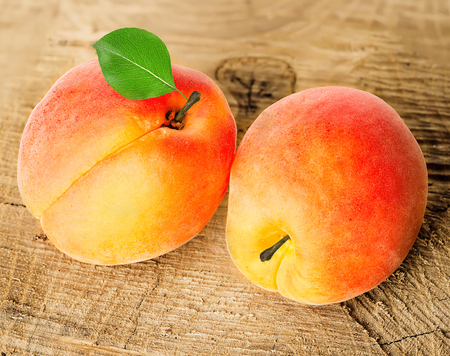 apricot kernel: Ripe apricots with leaf close-up on a wooden background.