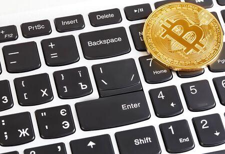 Golden bitcoin on keyboard. New virtual money.