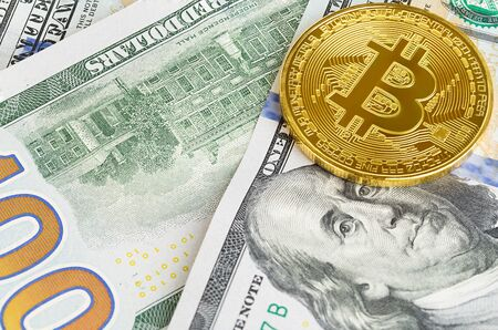 Two coins of bitcoin on banknotes of one hundred dollars. Exchange bitcoin cash for a dollar.
