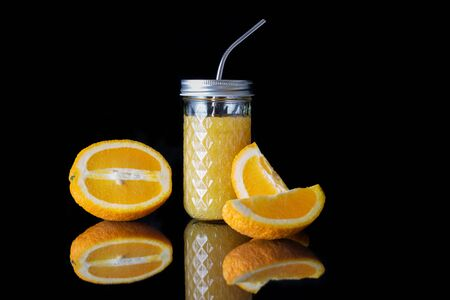 Effervescent refreshing orange drink in a glass cup with a metal tube and slices of orange on a black background with reflection