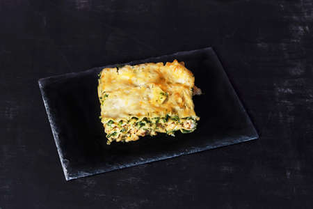 a piece of lasagna on a black background on a slate