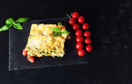 Traditional Italian dish of lasagna with meat, spinach, cheese close-up on a slate plate on a black background. horizontal
