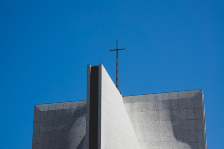 Architectural Detail Including Cross on a Modern Church Building Against Blue Sky