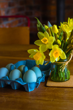 Blue Eggs and Yellow Daffodils on a Wooden Table in Springtime