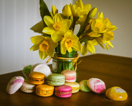 Macarons and Meringues on a Country Kitchen Table With a Bouquet of Fresh Daffodils Stock fotó