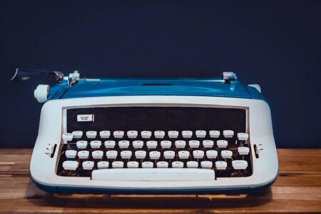 Close Up of Vintage Typewriter on Wooden Desk With Black Background