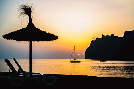 Silhouetted Thatched Sun Shade with Loungers in the Foreground of a Silhouetted Sailboat at Sunrise on the Mediterranean