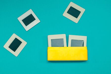 Retro 35mm Slide Photo Collection in Vibrant Yellow Box on Turquoise Background Foto de archivo - 129827223