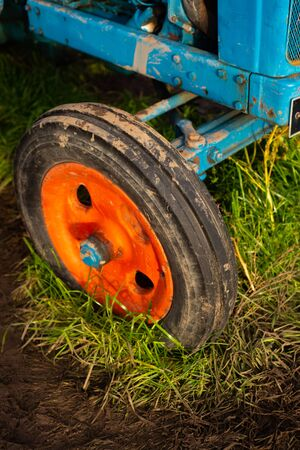 Detail from a Muddy Old Fashioned Tractor in a Field on a Farm