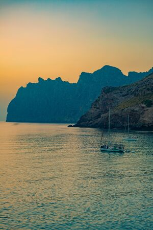 Sunrise Behind Dramatic Cliffs With Sailboats on the Mediterranean Sea Stock Photo
