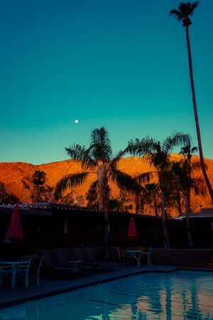 Mountains and Moon in the California Desert at Night With a Motel Pool and Palm Trees on the Foreground