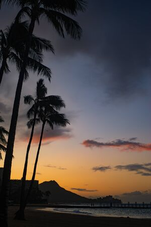 Sunrise Skies Behind Diamond Head on the Island of Oahu from Waikiki Beach With Palm Trees in the Foreground Stock Photo