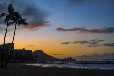 Palm Trees and Diamond Head Silhouetted at Sunrise from Waikiki Beach Hawaii Stock Photo