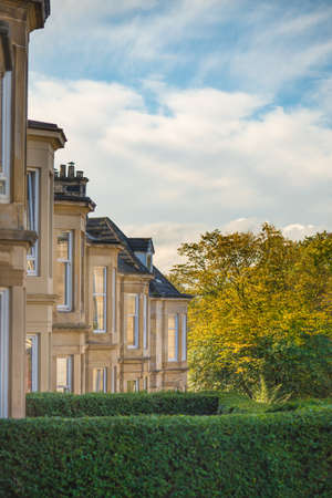 A Residential Street in Glasgow with Sandstone Terrace Houses and Autumn Leaves